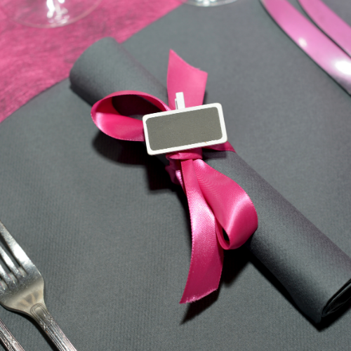 grey placesetting with pink ribbon and silverware