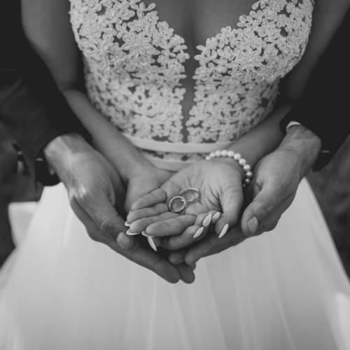wedding couple holding hands in front of bride with groom behind her