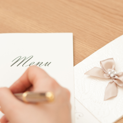 hand writing the words menu on a piece of paper