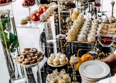 buffet of desserts on a long table at a wedding