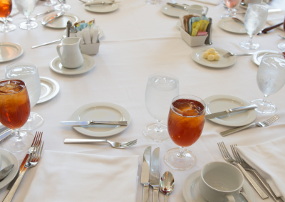round table with a white tablecloth plates and water glasses filled with juice