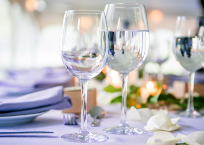 long table lined with glasses and plates in white