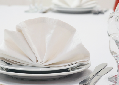 white plates with white napking fanned in the center of the plate