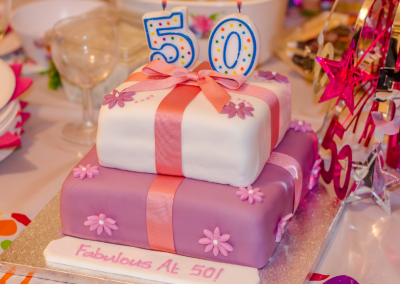 50th birthday cake 3 layers decorated in pinks and purples